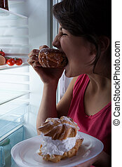 Girl eating doughnut and looking into a fridge
