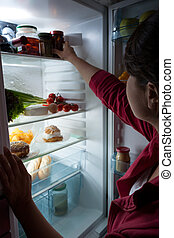 Hungry woman choosing food at the night