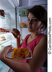 Gluttony at the night - woman against the fridge