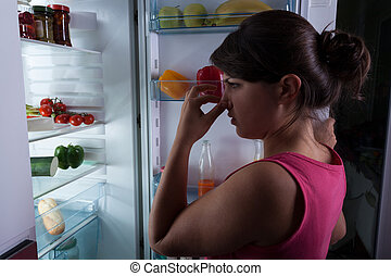 Woman holding nose - Woman standing against the fridge...