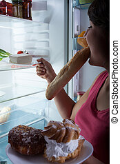 Girl suffering from bulimia choosing food from refrigerator