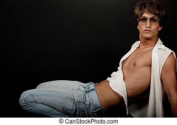 Hot young male model on black background