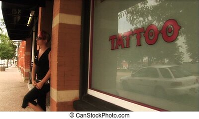 (1112) Tattooed young woman with Mohawk in front of Tattoo Parlor