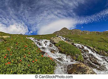 Beautiful mountain landscape with a mountain stream, the blue sk