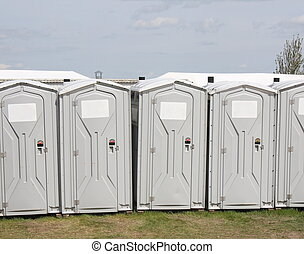 Portable Toilet Row - A row of portable toilets with blank...