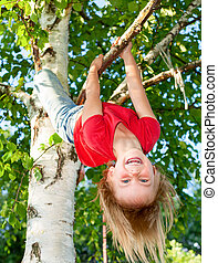 Child hanging from a tree branch - Little girl having fun...