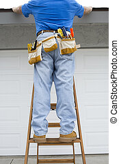 Contraqctor inspecting roof - A contractor stands on a...