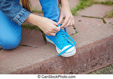 Tying shoelace - Hands of little girl tying lace of her shoe...