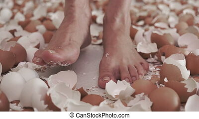 Standing Among Eggshells - Feet standing on a floor covered...