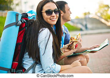 Having snack - Pretty traveler looking at camera with smile...