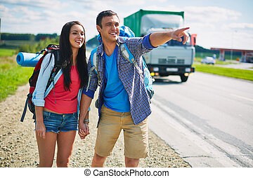 Hitch-hikers by highway - Couple of young hitch-hikers...