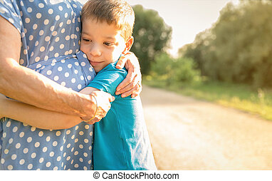 Grandson hugging to his grandmother outdoors - Portrait of...