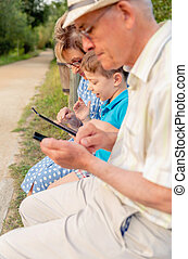 Grandchild and grandmother using a tablet outdoors - Closeup...