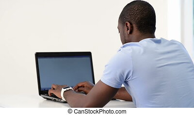 Young african-american man using laptop at home on the floor
