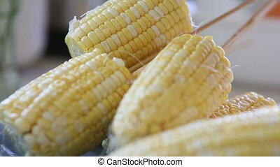 corn strung on wooden skewers and put on a plate