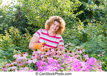 pretty woman looks after behind plants in garden - Young...