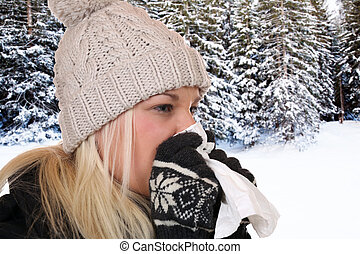Young woman with a cold and flu virus sneezing into a tissue...