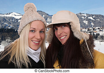 Two smiling women on winter holidays in the mountains