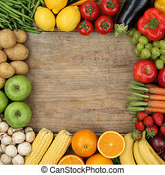 Fruits and vegetables forming a frame on a wooden board with cop