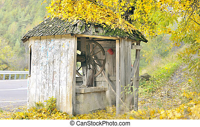 old fountain on autumn time - old fountain with shingle roof...