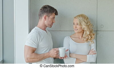 Young Couple Having Serious Discussion While Morning Coffee...