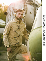 Young pilot posing near the helicopter - Young serious pilot...
