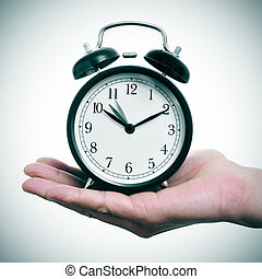 adjusting backward the clock - someone holding an alarm...