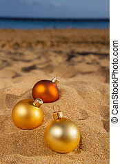 christmas balls on beach - three golden christmas balls on...