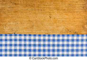 Rustic wooden background with a blue checkered tablecloth