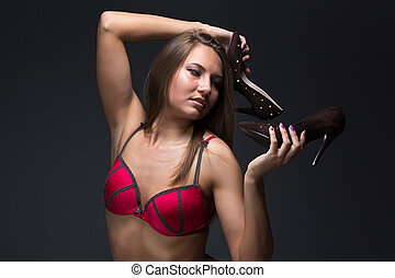 Portrait of young woman looking at shoes on black background