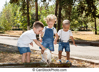 Group of happy children playing in park. Summer green nature...