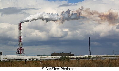 Air pollution by smoke coming out of factory chimney