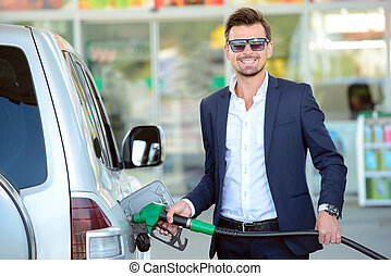 Petrol filling station - Young businessman refueling car...
