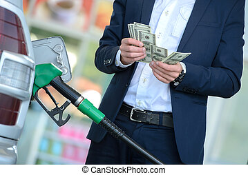 Petrol filling station - Businessman counting money with...