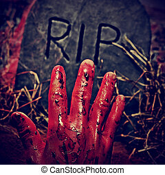 Halloween grave - closeup of a grave with a bloody hand in a...