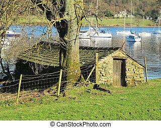an old stone boatshed beside a lake