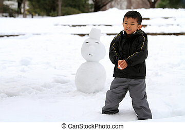 Japanese boy having snowball fight and snowman
