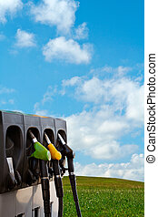 Nature and energy - Three gas pump nozzles over a nature...