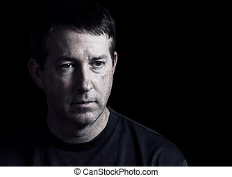 Mature man expressing negative emotions on dark background -...