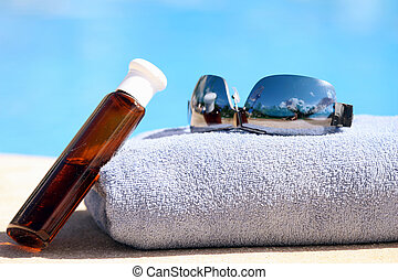 Sunglasses, towel and oil bottle by the swimming pool
