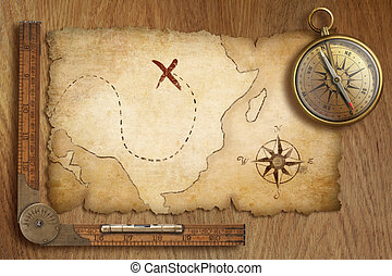aged treasure map, ruler and old gold compass on wooden...
