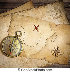 aged brass nautical compass on table with old treasure maps