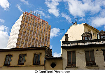 Old & new - Modern office building behing old houses at the...