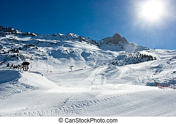 Empty ski slope - Fresh ski slope with snowcat tracks in...