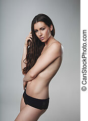 Topless young woman posing on grey background - Topless...