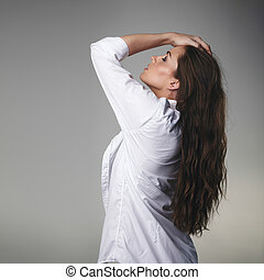 Passionate young brunette on grey background