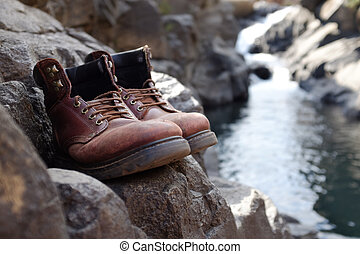 Limited focus old hiking boots in front of waterfall -...