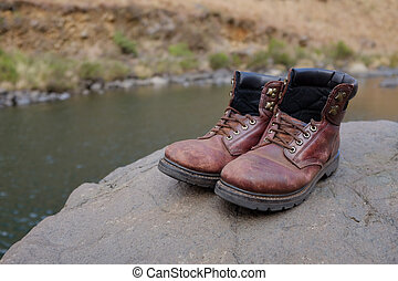 Old hiking boots beside river - Pair of old hiking boots on...