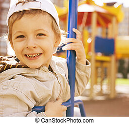 little cute boy on swing outside, playground background,...