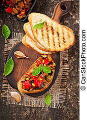 Bruschetta caponata with raisins and pine nuts decorated...